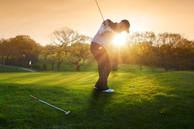 a lone golfer chips onto the green , the low sun is coming from behind him and flaring to camera.